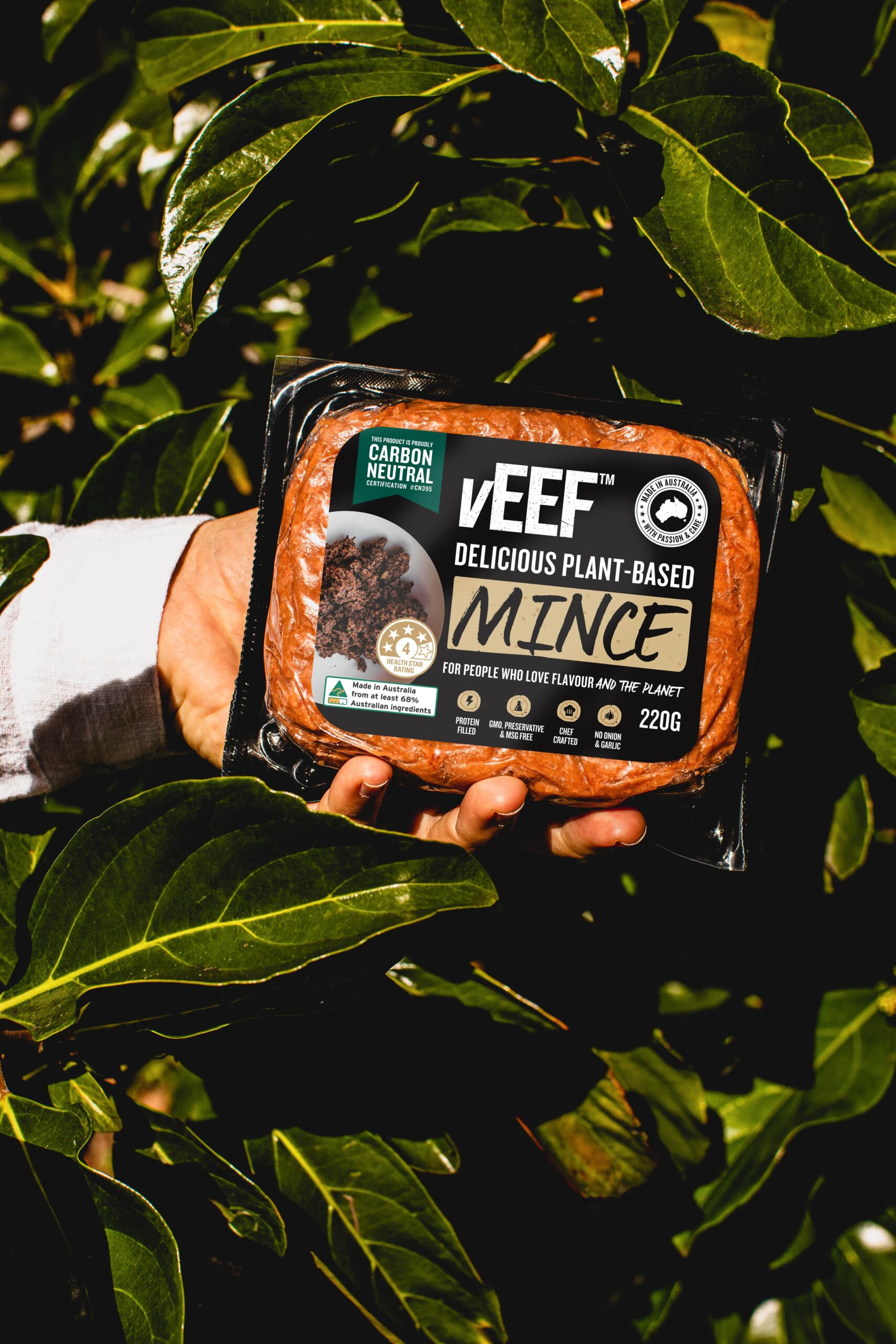 Hand holding vEEF Carbon Neutral Mince against greenery